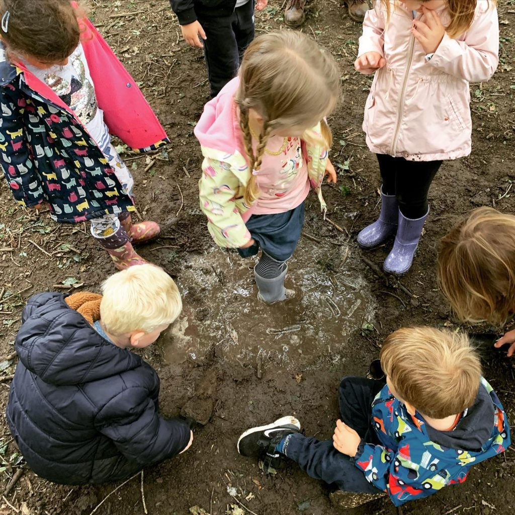 Children playing in a muddy puddle